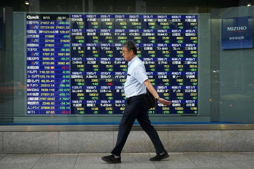 File photo of a pedestrian walking past a stock indicator board for the Tokyo Stock Exchange in Tokyo, on Aug 13, 2018.