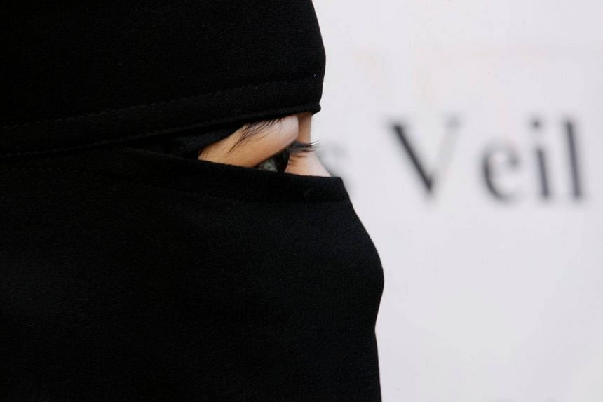 File photo showing a woman in a burqa taking part in a demonstration outside the French Embassy in London.