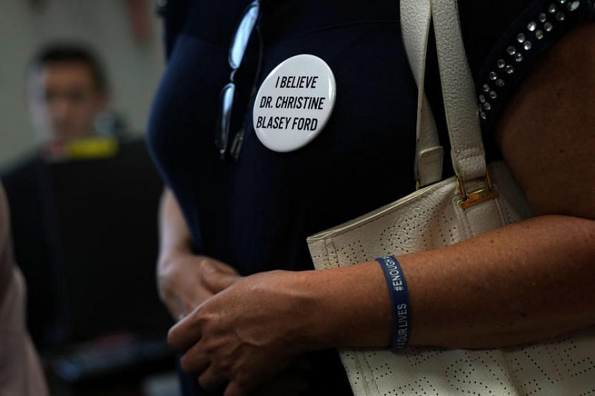 An activist wears a button in support of Christine Blasey Ford, who has accused Supreme Court nominee Judge Brett Kavanaugh of sexual assault at a high school party about 35 years ago, during a protest on Capitol Hill in Washington, on Sept 20, 2018.