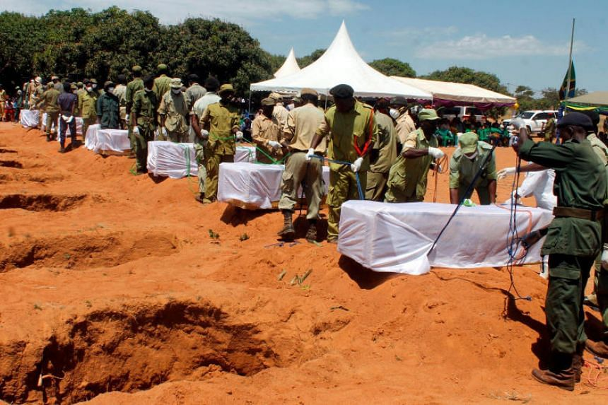 Tanzanian security agents prepare to bury the coffins containing the bodies of passengers retrieved after the MV Nyerere ferry overturned off the shores of Ukara Island in Lake Victoria, Tanzania, on Sept 23, 2018.
