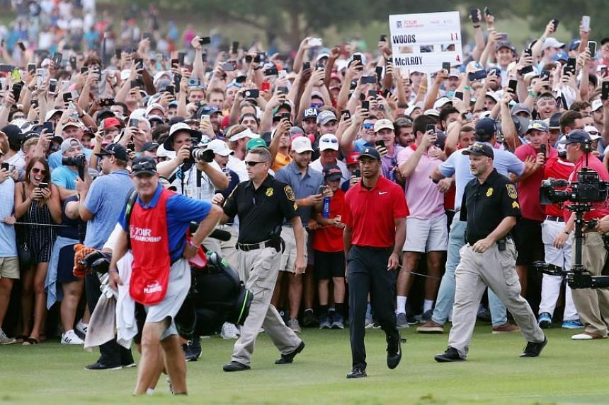Tiger Woods is swarmed by fans as he walks to the 18th green during the final round of the Tour Championship in Atlanta, Georgia, on Sept 23, 2018.