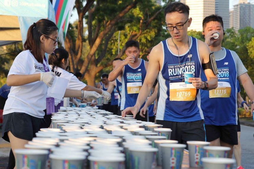 Volunteers handing out water and 100Plus drinks to runners taking part in the 10km race along Republic Avenue.