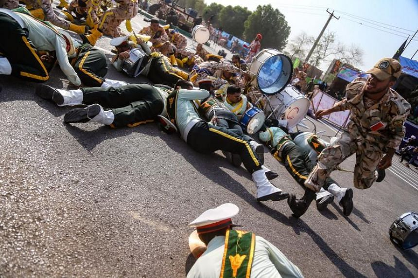 A soldier running past injured comrades lying on the ground at the attack on a military parade in Ahvaz, Iran, on Sept 22, 2018.