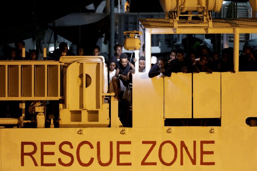 A file photo taken on Aug 25, 2018, shows migrants waiting to disembark from an Italian coast guard vessel at the port of Catania in Italy.