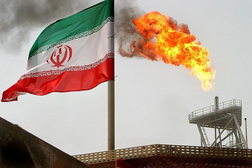 The Iranian flag flying on an oil production platform in the Soroush oil fields in the Persian Gulf. Commodity traders Trafigura and Mercuria yesterday said Brent could pass US$100 early next year, as markets tighten once US sanctions against Iran ar
