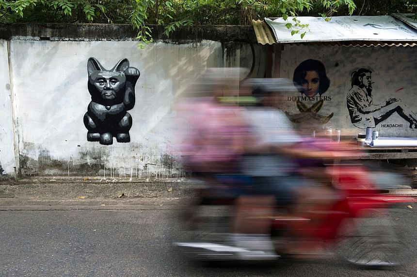 """A caricature by street artist Headache Stencil of Thailand's junta chief - depicted as """"a lucky cat"""" with a paw raised to rake in money - is spotted on a wall on Sept 4. Headache's work has caught the imagination of a country where an increasing numb"""