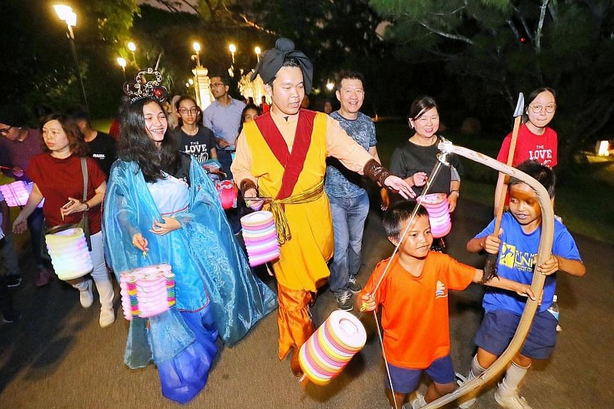 Performers dressed up as Chinese folklore characters Chang Er and Hou Yi leading Ryan Dinzly Naiman (in orange top), nine, Syahfril Hans (in blue top), 10, and other beneficiaries of the President's Challenge for a tour of the Istana grounds yesterda
