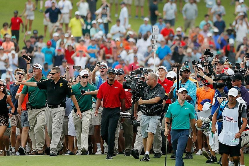The massive gallery at Atlanta's East Lake Golf Club chanting Tiger Woods' name as the sport's biggest star returns to the winner's circle. Walking ahead on the 18th green is flight-mate Rory McIlroy.
