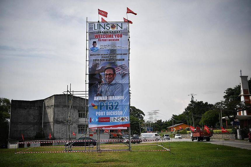 """A poster in Port Dickson with Datuk Seri Anwar Ibrahim's image. Mr Anwar is expected to win the by-election easily, but Umno president Ahmad Zahid Hamidi said Barisan Nasional viewed the seat as being vacated """"to fulfil the political ambitions of one"""