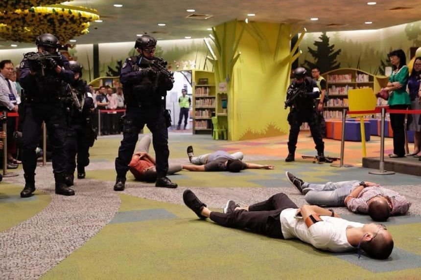 Police officers conduct a search after apprehending a masked gunman during Exercise Heartbeat at the National Library on Sept 25, 2018.