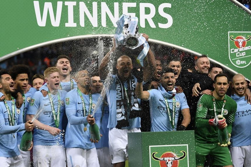 Manchester City players celebrate with the trophy after winning the English League Cup final against Arsenal at Wembley Stadium in London on Feb 25, 2018.