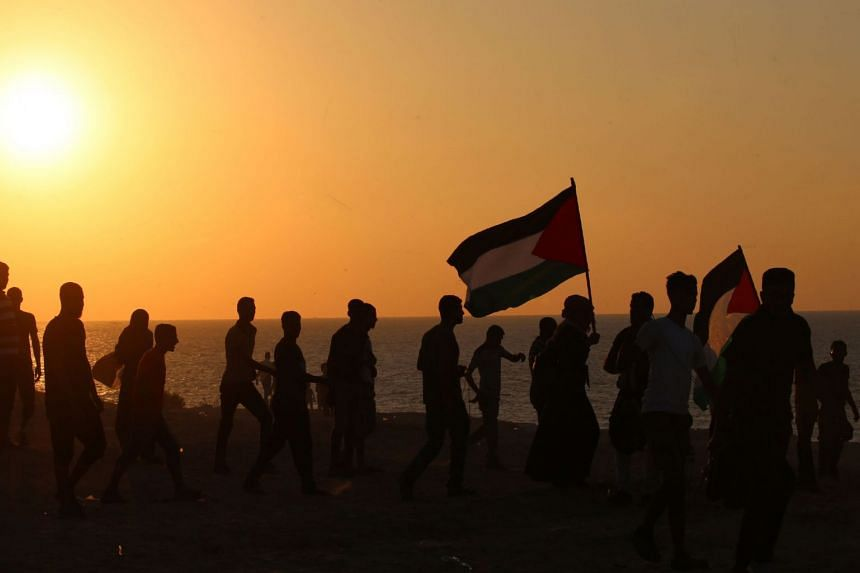 Palestinian demonstrators carry national flags during a protest calling for an end to the Israeli blockade on Gaza. Gaza's economy shrunk by 6 per cent in the first quarter of 2018, said the World Bank.