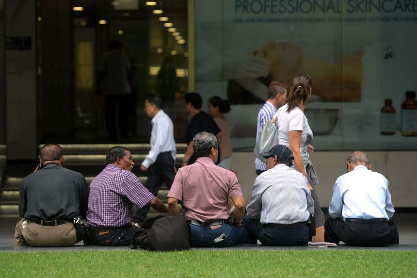 A group of elderly men sitting outside Raffles Place MRT station. A survey by the Economist Intelligence Unit found that respondents plan to continue working after they turn 62 - the standard retirement age.