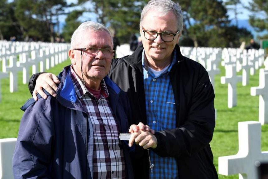 Andre Gantois (left), 72, a resident of Ludres, in eastern France, and Allen Henderson, 65, of Greenville, South Carolina, pose with their father's dogtag at the Normandy American Cemetery and Memorial, on Sept 24, 2018.