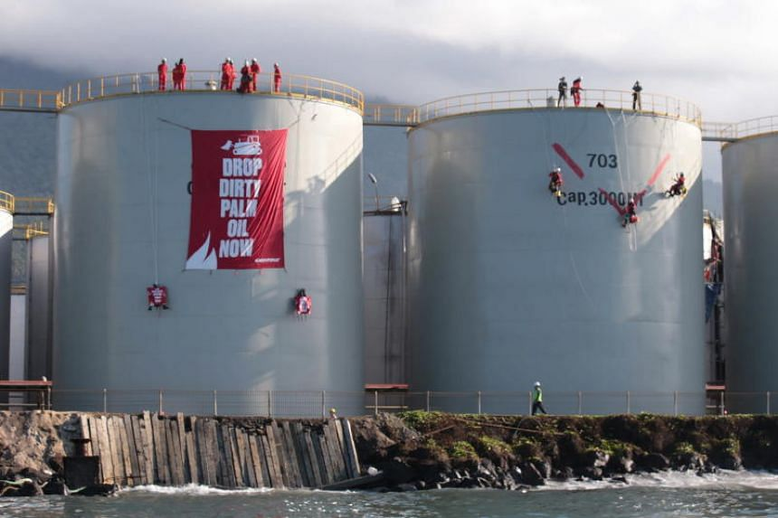 Greenpeace activists unfurl a giant banner on a tank of Crude Palm Oil and paint another at a Wilmar Group port in Bitung, North Sulawesi, Indonesia, on Sept 25, 2018.
