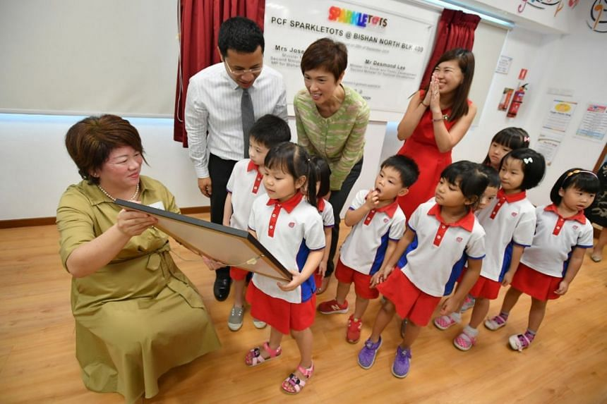 Ms Delphine Teo (left), Lead Executive Principal, and five-year-old Maggy Lim Mei Qi, showing Minister for Social and Family Development Desmond Lee and Manpower Minister Josephine Teo tokens of appreciation.