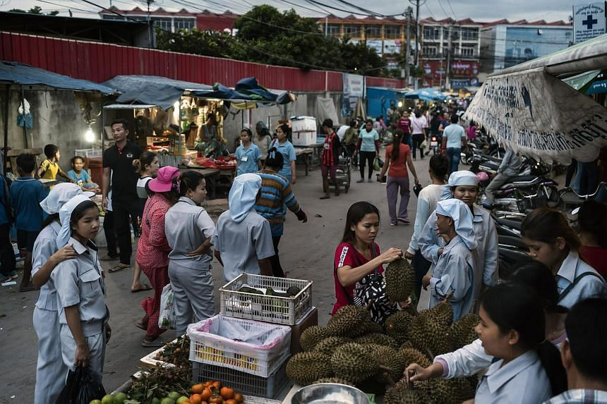 Factory workers walk past street vendors at the end of their shift in a special economic zone in Phnom Penh, Cambodia, on July 27, 2018.