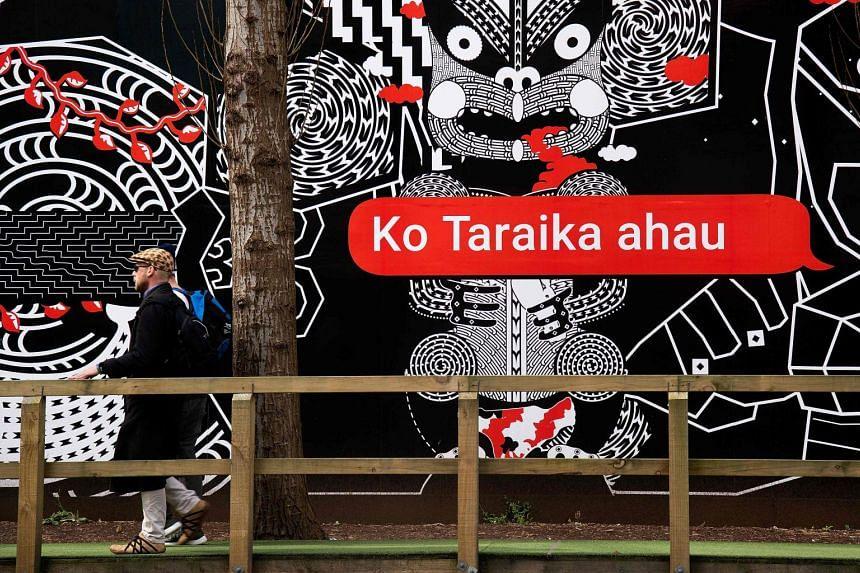 People walk past Maori language signs in Wellington, on Sept 13, 2018.