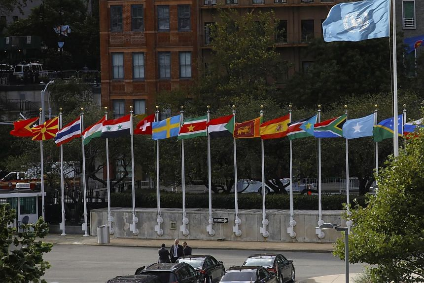 Flags fly above diplomatic vehicles on the first day of high-level meetings at the United Nations headquarters in New York, on Sept 24, 2018.