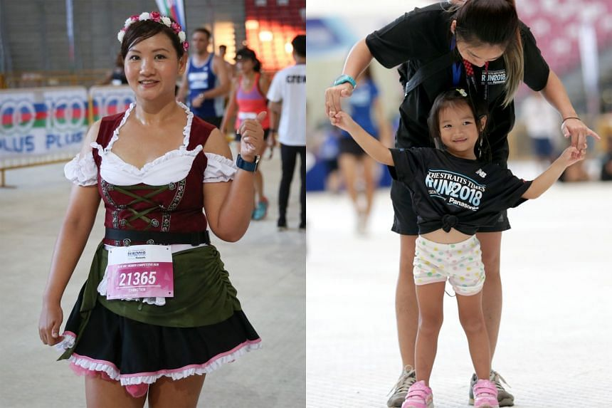 Left: A runner spotted after the finish line in a dirndl, a traditional German dress in anticipation of Oktoberfest. Right: Four-year-old Mathilda Huang dancing to the beat during the fitness workout at the Sports Hub after completing the ST Run 5km