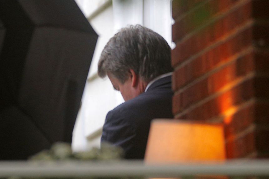 Kavanaugh leaves his house as US Marshalls try to hide him from cameras with an umbrella.