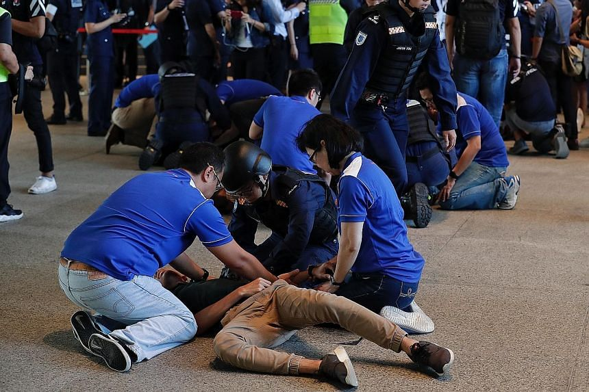 """National Library Board staff (in blue) rendering aid to """"casualties"""" as Singapore Civil Defence Force officers arrive during the drill at the library. Above: A masked gunman """"exchanging fire"""" with police officers during Exercise Heartbeat in the chil"""
