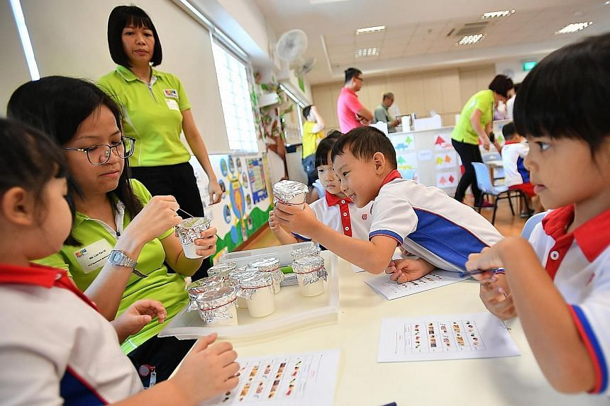 Wang Linjia, five, holding up a cup to smell its contents and guess the substance during a lesson at PCF Sparkletots @ Bishan North Block 409. Muhammad Farid Rizqi Abdullah (centre), 15 months old, and Nur Raiqa Izziyara Muhammad Iswandy (behind him)