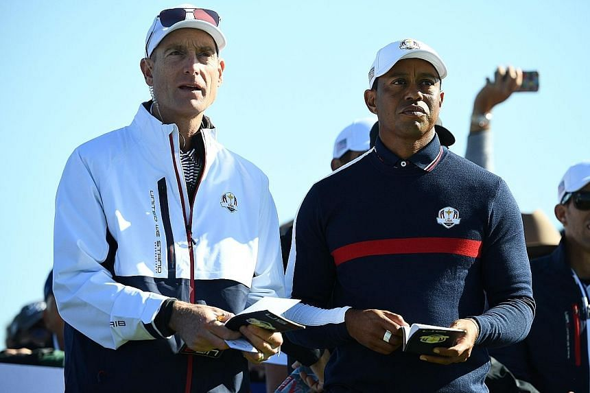 Tiger Woods speaking with US Ryder Cup team captain Jim Furyk during a practice session at Le Golf National Course, south-west of Paris yesterday. The biennial tournament against Europe starts on Friday.