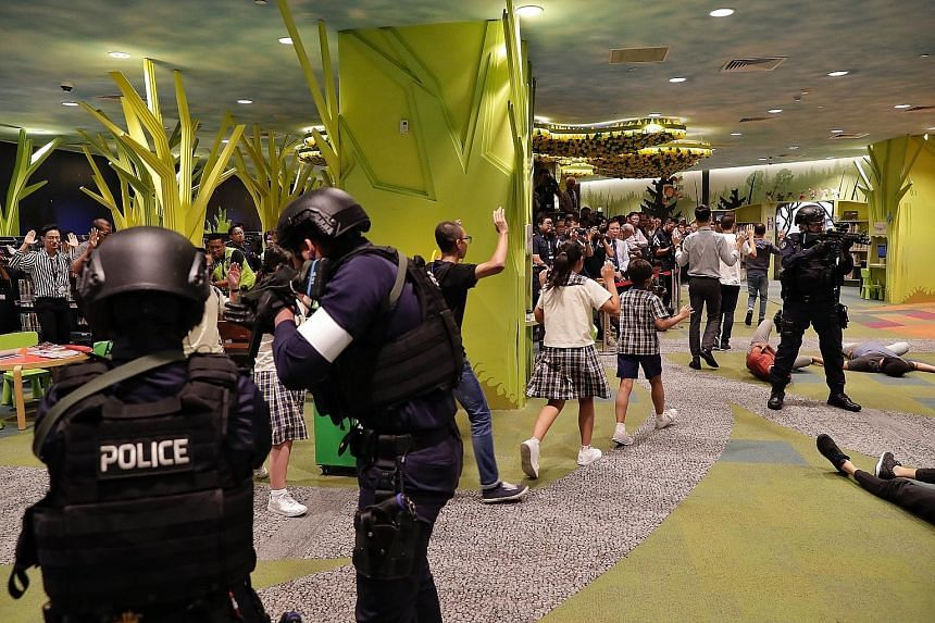 Police ushering library users to safety during anti-terror drill Exercise Heartbeat at the National Library Building yesterday. In analysing a survey from last year of just over 2,000 Singaporeans, researchers also found that older and less well-off