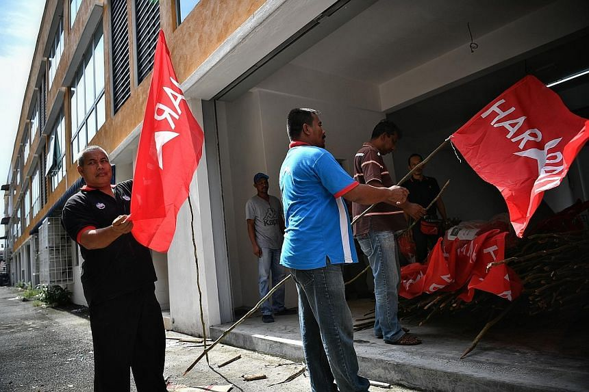 Above: Parti Keadilan Rakyat supporters preparing the command centre for the Oct 13 by-election in Port Dickson. Left: Residents of Port Dicksonare hoping Datuk Seri Anwar Ibrahim's expected return to Parliament will usher in a new period of growth a