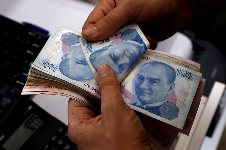 A money changer counts Turkish lira banknotes at a currency exchange office on Aug 2, 2018.