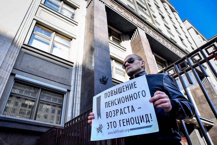 """Russian opposition leader Sergei Udaltsov holds a poster reading """"Retirement age increase is genocide!"""" against President Vladimir Putin's pension reform in front of the State Duma in Moscow on Sept 26, 2018."""
