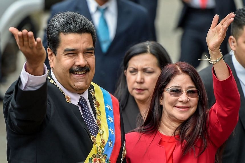 Venezuelan President Nicolas Maduro (left) and his wife, Cilia Flores waving to supporters at a January 2017 event.
