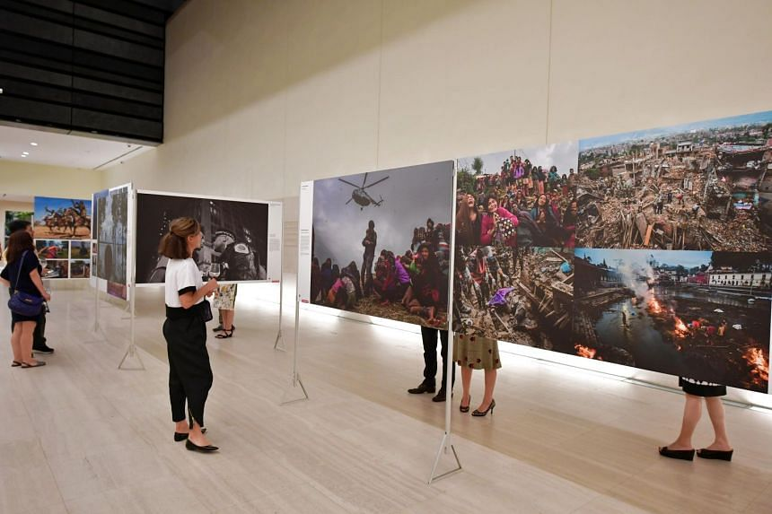 Guests look at the photos being exhibited at the World Press Photo exhibition held at the National Museum of Singapore, on March 2, 2017.