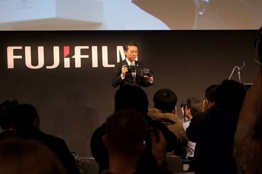 Fujifilm's optical device and electronic imaging product division general manager Toshi Iida showing off the new medium-format rangefinder GFX 50R at a press conference a day before the start of Photokina 2018.