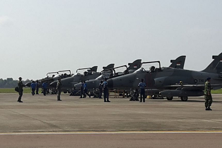 Indonesian Air Force Personnel stand near a line up of five Hawk fighter jets in Hang Nadim Air Base in Batam, on April 3, 2018.