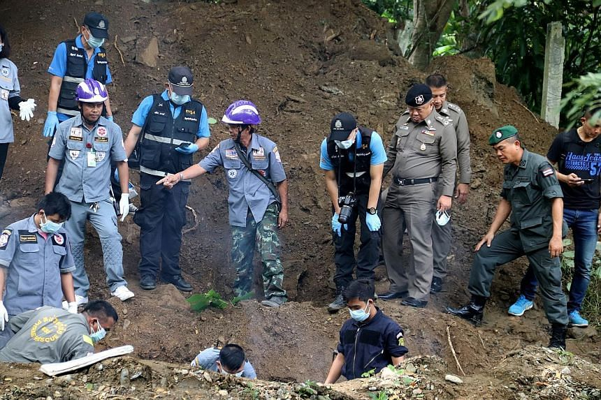 Thai police and workers recovering the bodies of Mr Alan Hogg and his Thai wife Nhot Suddaen, who were found buried in 2m-deep graves on their property in the province of Phrae after allegedly being killed by hitmen.
