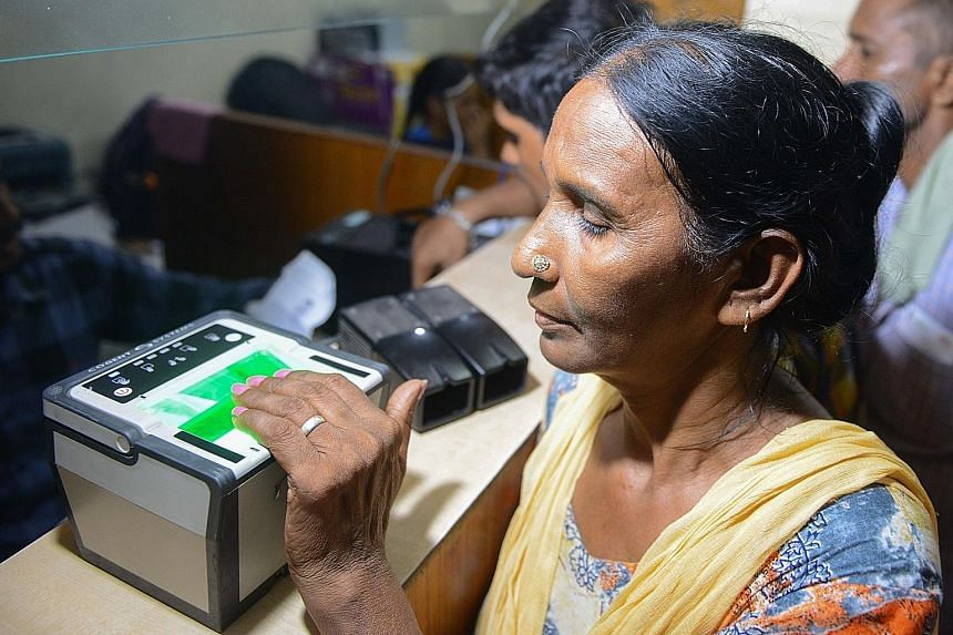 A woman getting her fingerprints read while registering for Aadhaar, which has provided biometric identities to over a billion people.