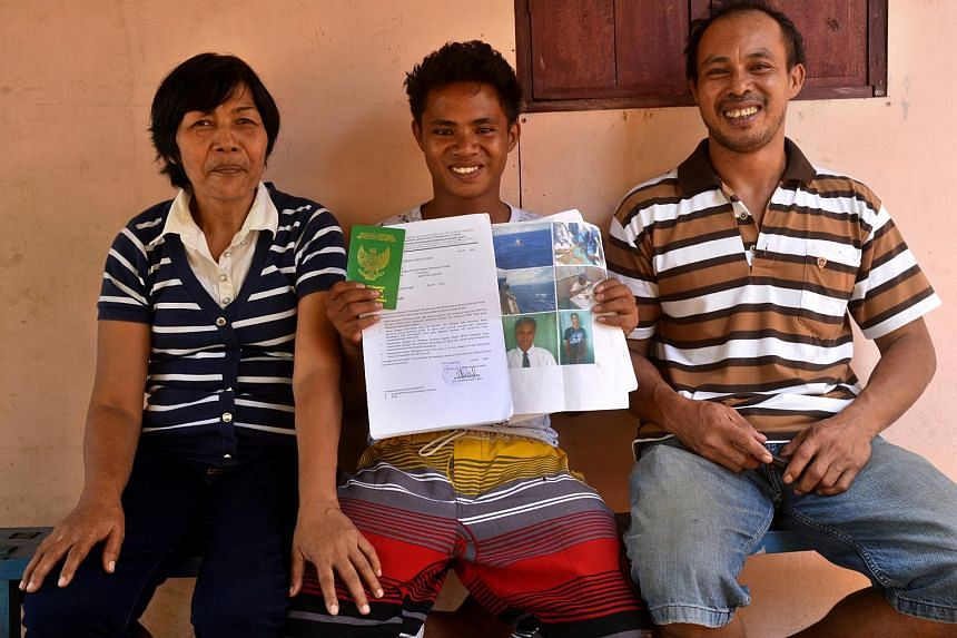 Aldi Novel Adilang (centre) poses with his parents as he shows his pictures of being rescued by the Japanese Coast Guards in Guam waters in North Minahasa, Indonesia, on Sept 25, 2018. He said his two earlier experiences of being stranded at sea were