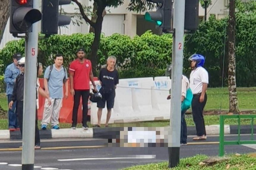 A photo sent to citizen journalism website Stomp shows the aftermath of the accident in Woodlands Avenue 3 on the evening of Sept 26, with the man lying on the road and several onlookers standing nearby.