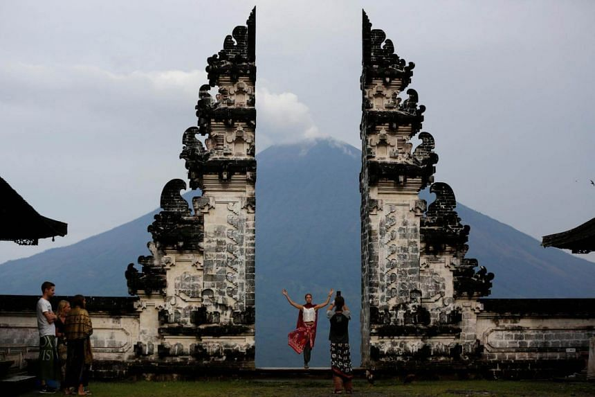 Tourists visit Lempuyang temple which overlooks Mount Agung volcano, in Bali, Indonesia, on Dec 3, 2017.