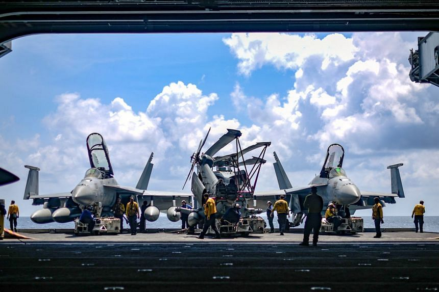US Navy sailors move aircraft from a lift into the hangar bay of the aircraft carrier USS Theodore Roosevelt in the South China Sea, on April 8, 2018.