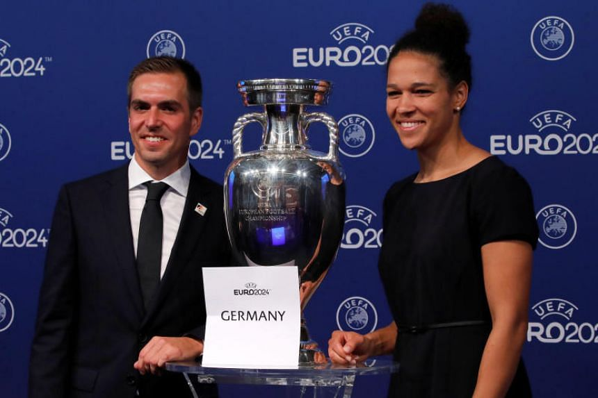 Germany's ambassadors for the European Championship, Philipp Lahm and Celia Sasic, pose with the Uefa trophy after it was announced that Germany was elected to host the Euro 2024 football tournament.