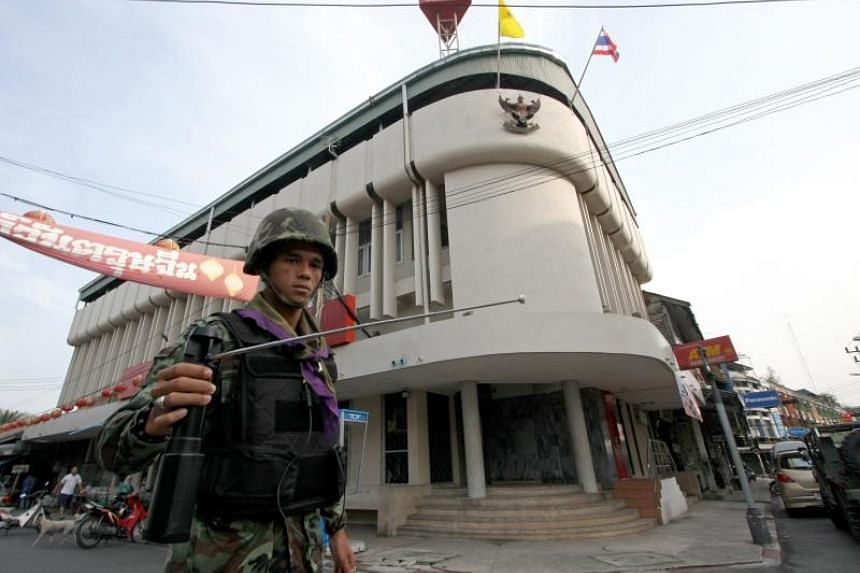 A file photo taken on March 2, 2010, shows a Thai soldier using a GT200 detector as he patrols the streets of Yala, in Thailand's restive south.
