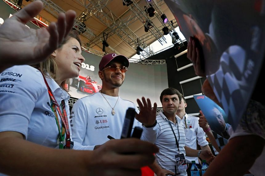 Hamilton (centre) attending an autograph session at the Sochi circuit ahead of the 2018 Russian grand prix.