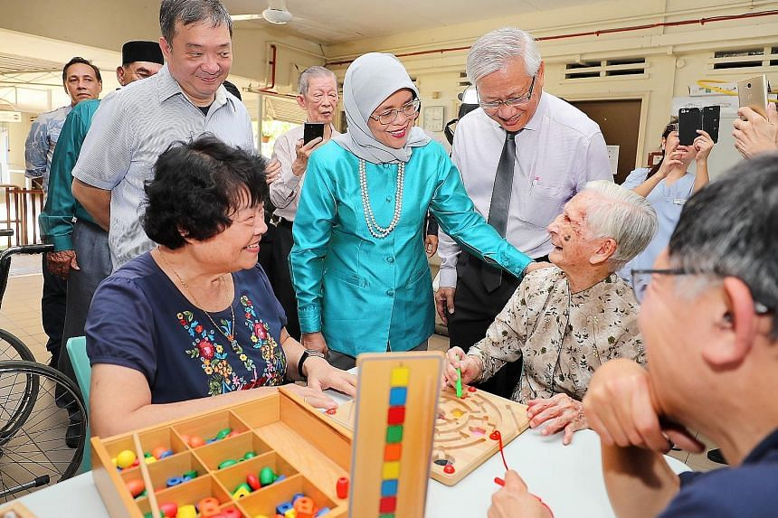 President Halimah Yacob chatting with St John's Home resident Tan Sing Choon, 93, and volunteer Anita Lin (left, in blue), 72, yesterday. Accompanying the President are Potong Pasir MP Sitoh Yi Pin (behind Madam Lin) and Mr Woon Wee Yim, the home's c
