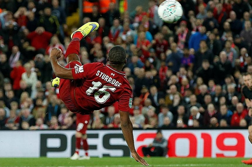 Above: Chelsea's Eden Hazard celebrates scoring their second goal against Liverpool. He shrugged off the attentions of four opponents before rifling home the winner that secured passage into the fourth round. Left: Liverpool's Daniel Sturridge had ea