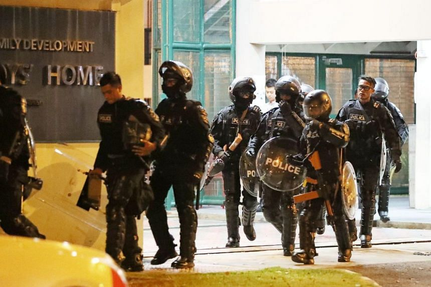 Police officers dressed in riot gear leaving the Singapore Boys' Home in Jurong West. The police received a call for assistance at 5.51pm on Sept 28, 2018.