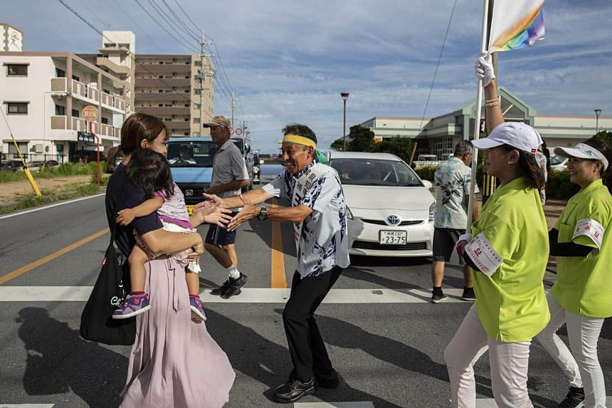 Former disc jockey Denny Tamaki (centre) is running for governor of Okinawa, the southern island chain that bears the brunt of the US military presence in Japan.