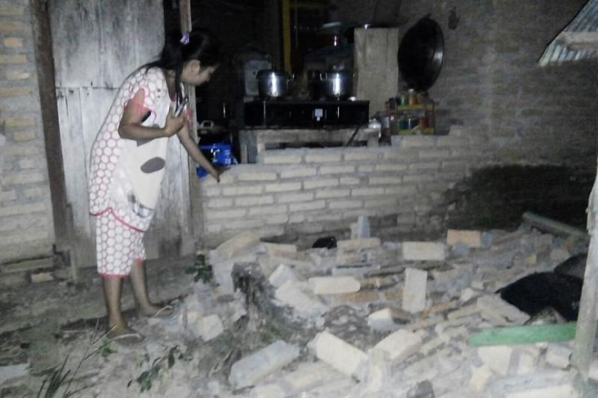 A resident is seen beside a collapsed brick wall of her house at in Central Mamuju, in Indonesia's western Sulawesi province, after a strong earthquake hit the area on Sept 28, 2018.
